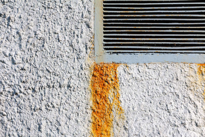 Edge of a rectangular ventilation grill in a roughly plastered concrete wall with rust stains. Industrial background