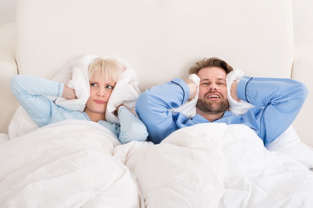 Couple Covering Ears While laying On Bed At Home