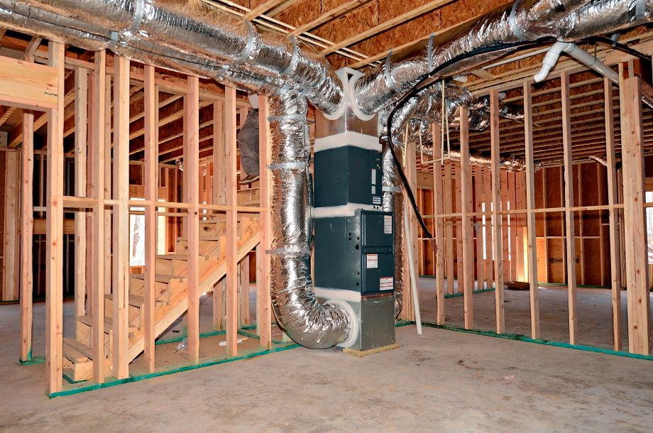 The newly framed basement area of a house. The central heat and air ductwork system is beside the stairs